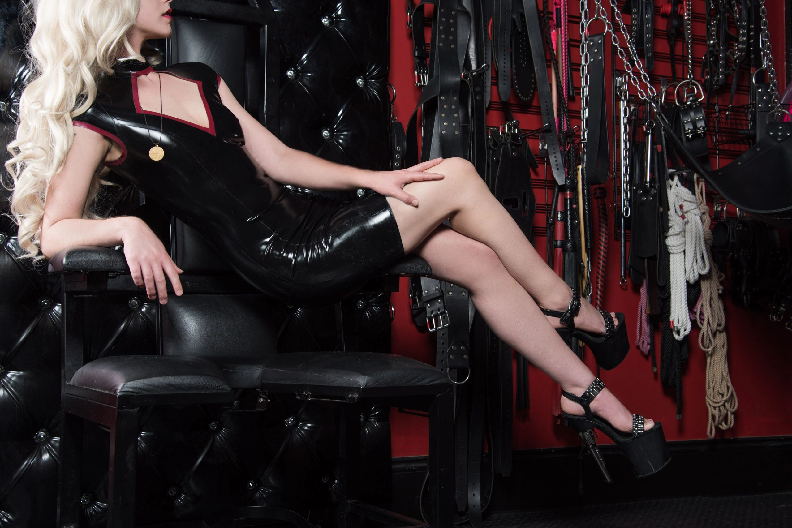 Mistress Samara, a white blond woman, wears a latex dress and reclines on a throne in a BDSM dungeon