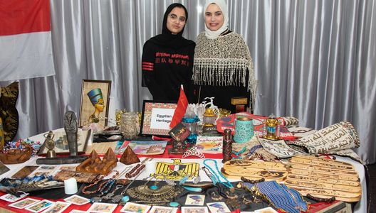 Two MACFEST volunteers stood behind and Egyptian Heritage cultural table at MACFEST 2020 festival