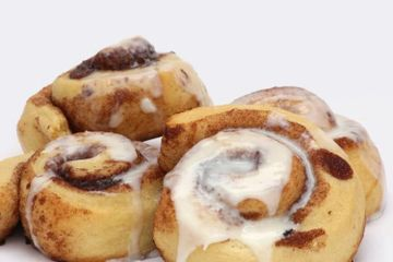 Warm cinnamon buns fresh baked and drizzled with vanilla icing.