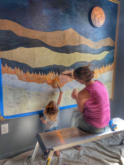 Connie works on an indoor paper mountain mural while her toddler daughter paints along with her.