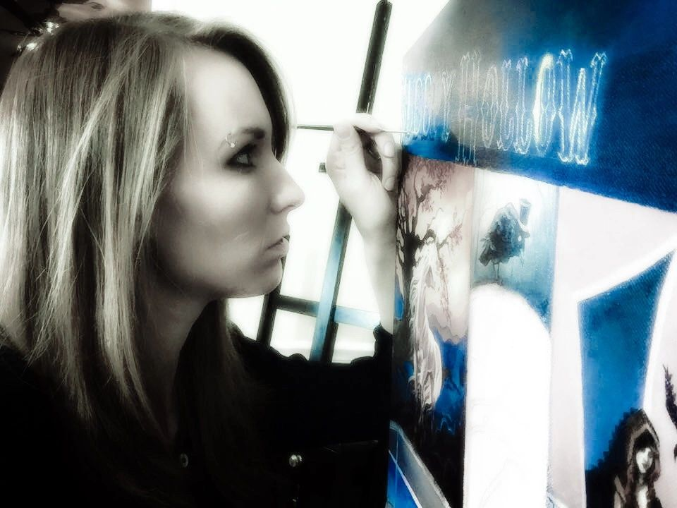 Connie stares intently at her canvas as she paints her latest oil piece