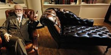 Sigmund Freud smoking cigar sitting on a chair next to psychotherapy couch.