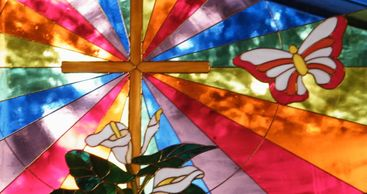 stained glass rainbow with cross, butterflies, and lilies