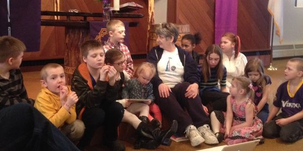 Adult leader talks with children on the altar step during worship