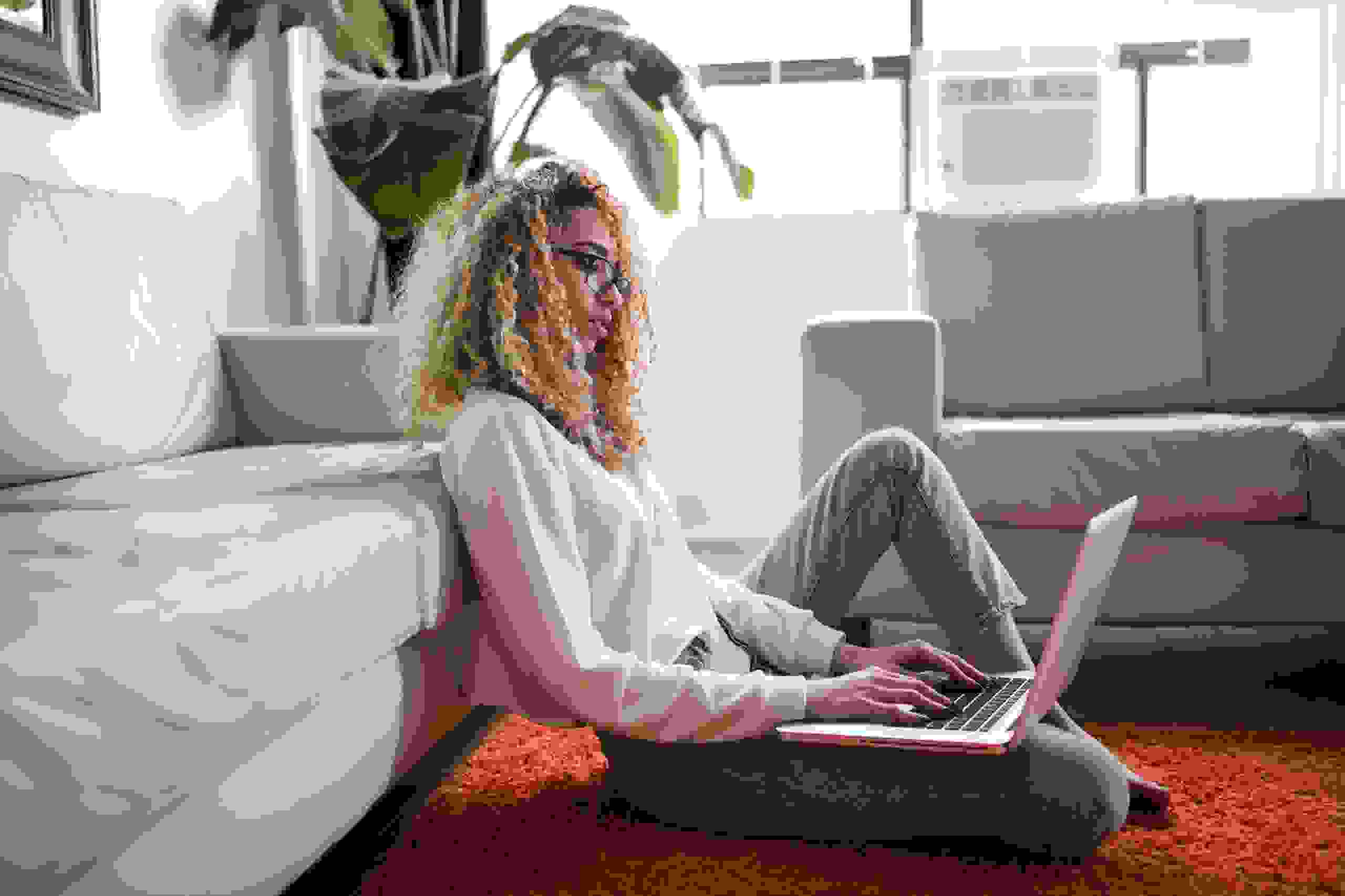 Young woman with curly hair sitting on the floor typing on her laptop.