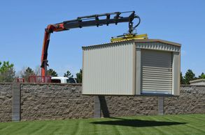 Storage building delivered over fence with a boom truck