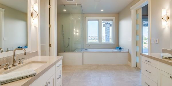 Master bathroom with glass shower and soaking tub. Tile floors and modern lighting.