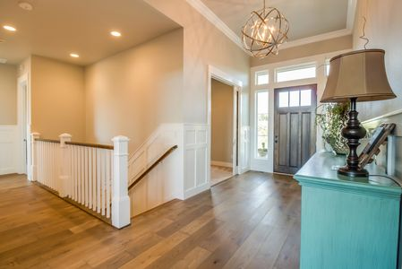 Entry to a custom home with tall ceilings, crown molding, and wainscot pannelling.