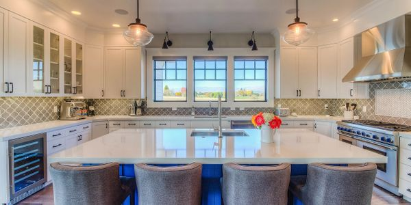 Custom kitchen with tile backsplash and blue island cabinets.