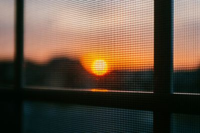 view of the sunset through a new window screen