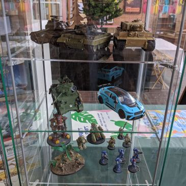 A display case featuring a range of painted model tanks and cars with some figurines