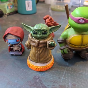 small painted models of popular culture figures - baby yoda, teenage mutany ninja turtles and mumra