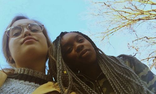 Selfie of two young adult women, white and black, looking confident and empowered. It is a sunny day