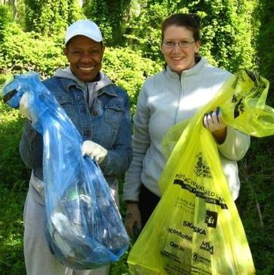 Two young stream cleaners with bags of trash and recyclables