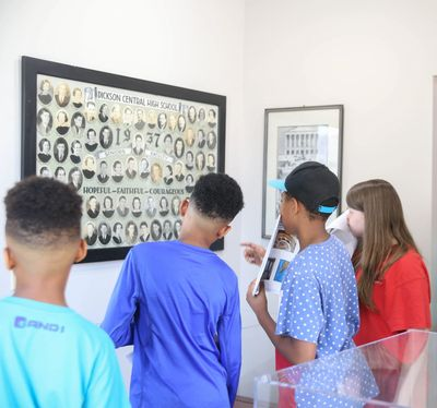 Group of kids looking at photographs in museum.