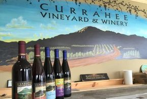 Photo of some Currahee wines in front of a mountain painting at the distillery.
