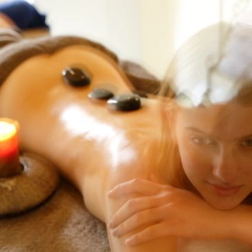 Lady at Day Spa with hot stones and candle for                          Restorative mobility & Holistic Bodywork