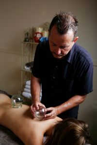 Remedial Therapist standing over client using cupping to help in holistic bodywork