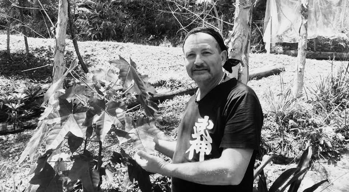 Sensei Shayne Harris Martial Artist standing in the garden with sacred Hawaiian Nut Tree