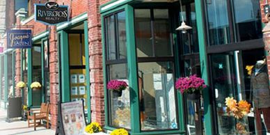 Brick Store Front on Main Street.  Large windows.  Decorated with flower pots.