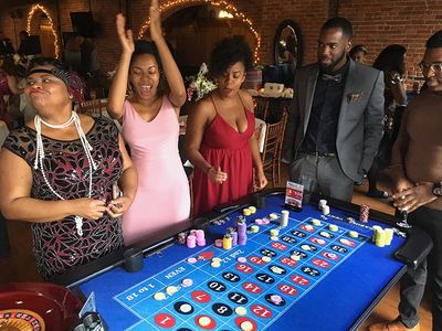 Amherst Casino Events' roulette table with excited guests at a 1920's theme casino night party.