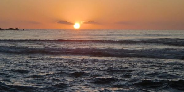 PHOTO OF THE PACIFIC OCEAN AT SUNSET WITH CLOUDS ON THE HORIZON