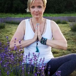 Beautiful woman sitting in a lavender field, hands in prayer, doing Yoga while wearing her Bohemian Zen Wear essential oil diffuser gemstone bracelets and necklace