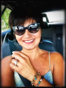 Beautiful woman in a car smiling wearing her gemstone bracelets made by Bohemian Zen Wear