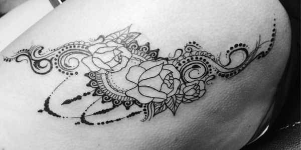 Mandala and rose tattoo on a woman's thigh in black and white