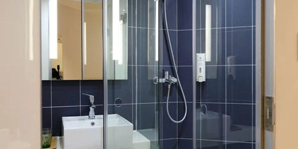 Very comfortable glass-enclosed shower. Ceramic sink on an easy to care for shelving system.