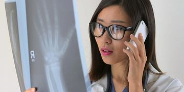 asian doctor phone computer glasses