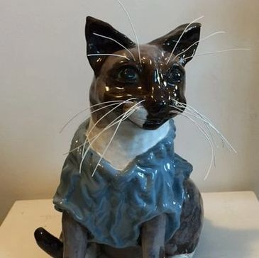 A sculpture of a Siamese cat wearing a blue sweater