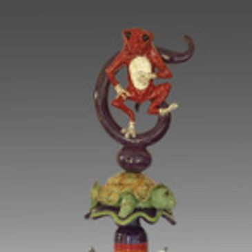 Totem Pole Sculpture with dancing red frog on the top