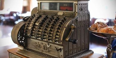 Image of an antique bronze manually-operated cash register, like one would have seen in the late 1800's or early 1900's. It sits on the counter of a shop