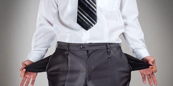 A man pulling both empty pockets out of his pants, showing he has no money.