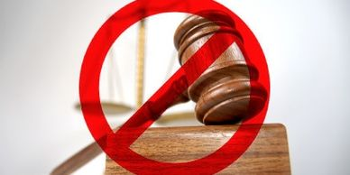 "Image of a gavel resting on a wooden stand, with a red circle and line superimposed over it, depicting ""no court"""