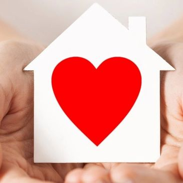 Graphic of hands holding a white paper cutout of a house, with a red heart on it