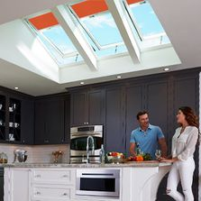 Orange blinds on venting skylights in gray kitchen