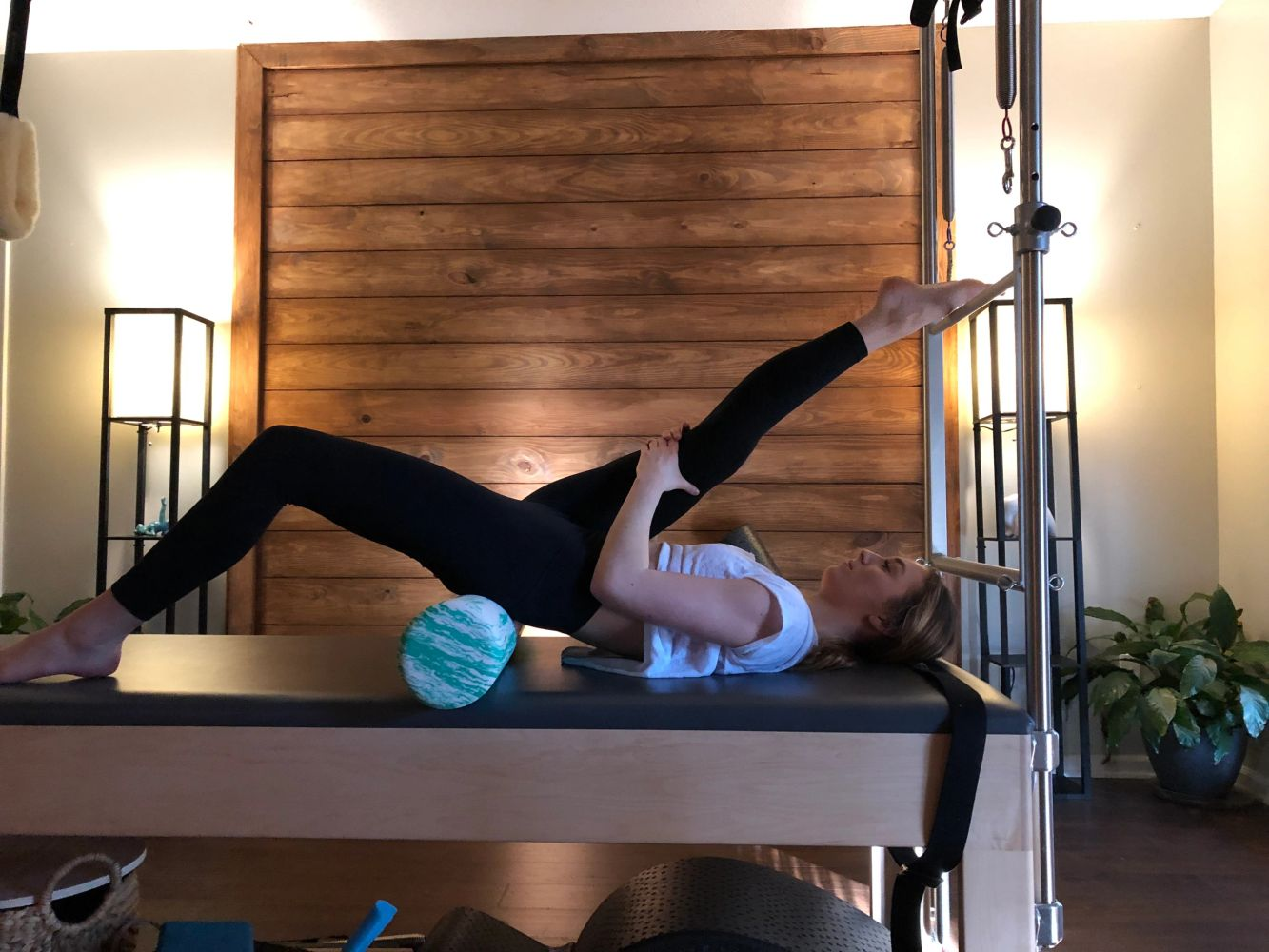 Stretching with the foam roller on The Cadillac at Pilates by Kim.