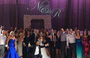 Happy Wedding party with a custom monogram in the background.