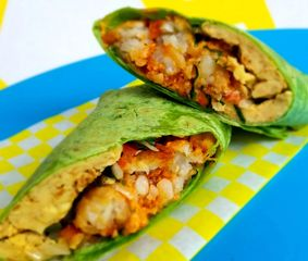 A burrito made with vegan JUST egg, tots, and sauces rolled into a toasted spinach tortilla.