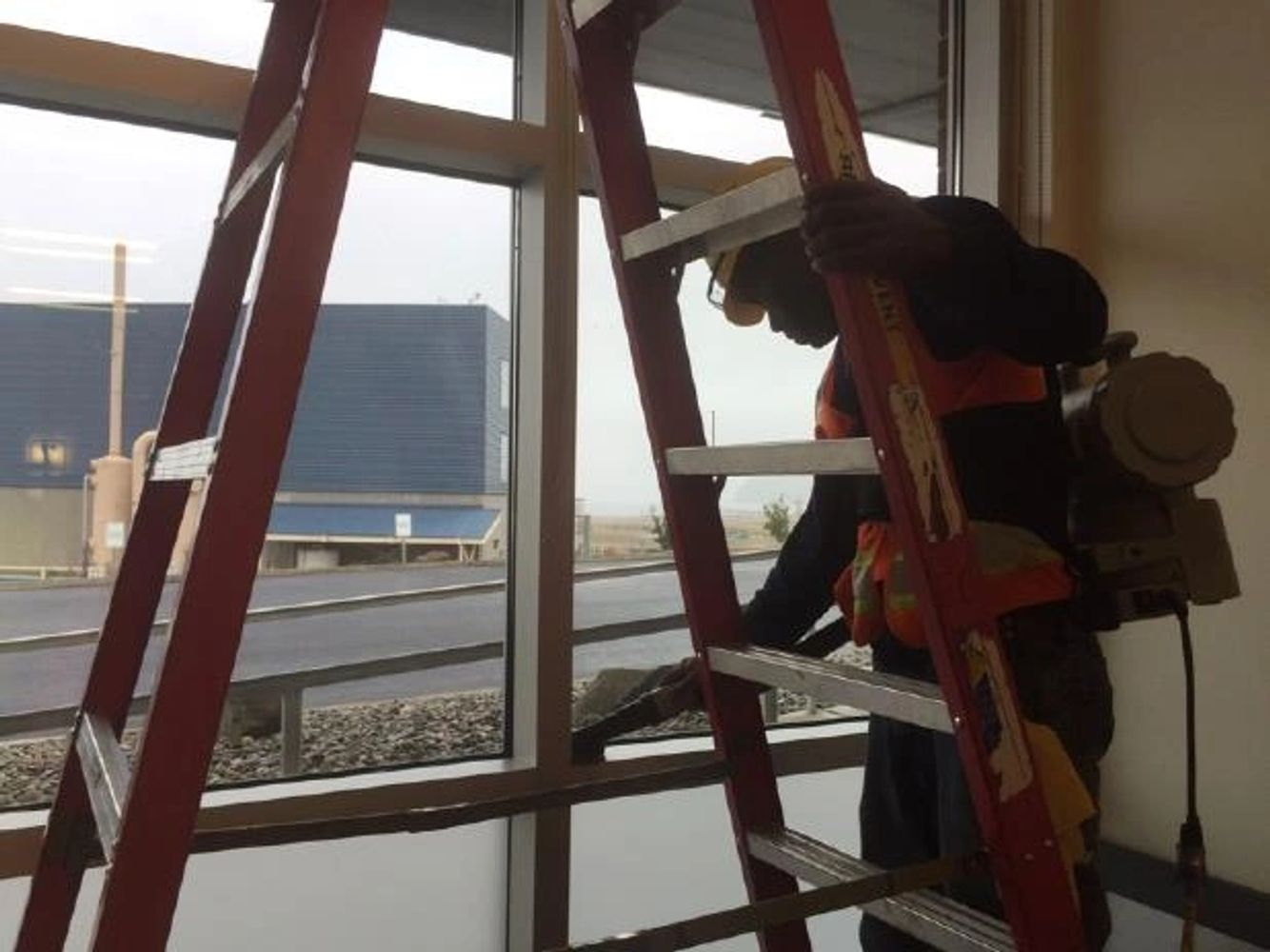 An image of an Accountable employee doing construction cleaning with a shock vacuum on a window sill