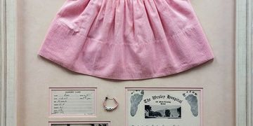 Testimonial for Art & Frame in Wichita with example of framing of baby dress and birth certificate.