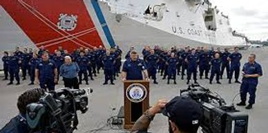 Coast guardsmen standing in formation with coast guard cutter in background.