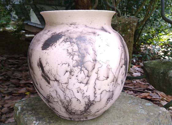 If you place horsehair onto a hot piece of pottery at the right time it results in the black marks.