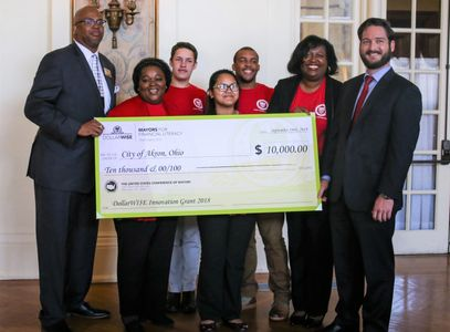 "Mayor's Youth Leadership member and advisors, accepts  grant supporting ""Teens and Money Workshops"""