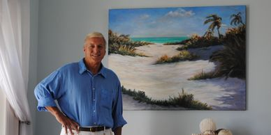 Tropical Artist, Alan Zawacki, with one of his original paintings in a customer's home