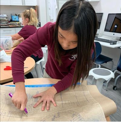 female student using a tracing wheel to trace a pattern