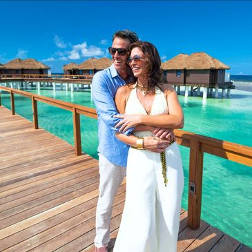Couple standing on dock to overwater bungalow