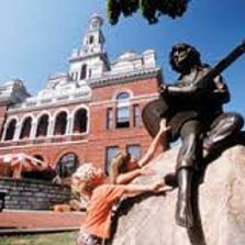 Child touching Dolly Parton's statue outside Downtown Sevierville, TN courthouse.